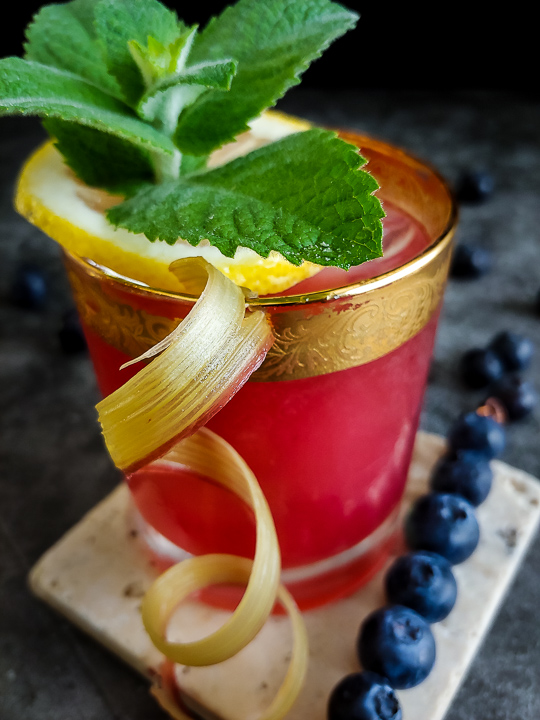 pink cocktail with rhubarb curl, mint and blueberry garnish