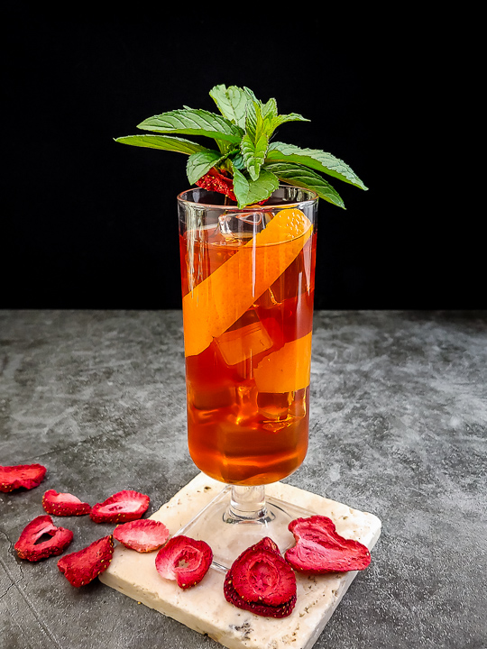 whiskey cocktail with strawberry, orange and mint garnish