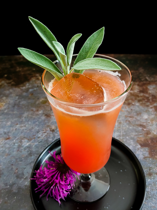 orange-hued whiskey sour with sage leaves and bee balm flowers