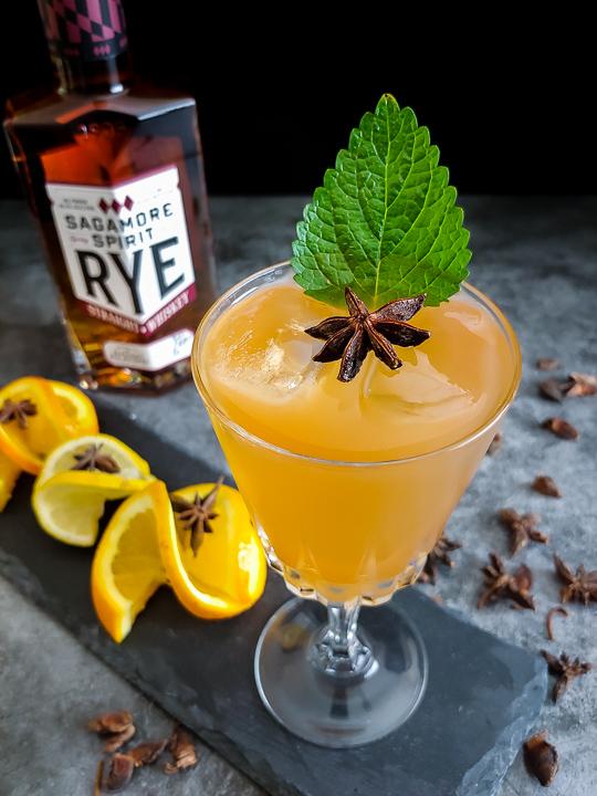 Orange sazerac with bottle of Sagamore Spirit Rye in the background