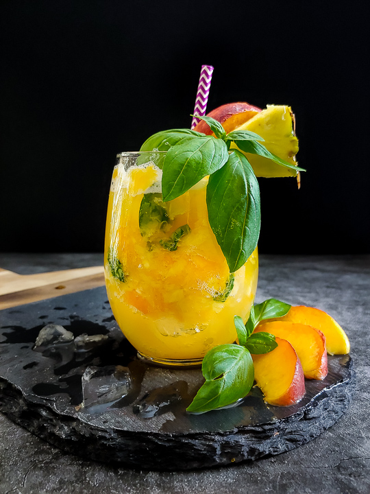 Pineapple Peach Smash with basil pineapple and peach garnish