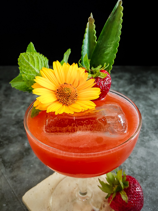 strawberry cocktail with fresh flowers, ming and strawberry garnish