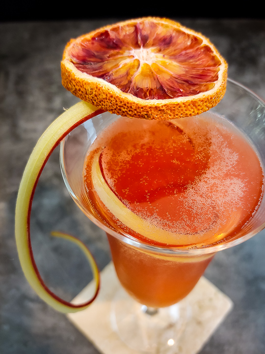 Aperol spritz cocktail with dried blood orange and rhubarb curl