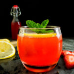 red cocktail with strawberry, mint and lemon garnish