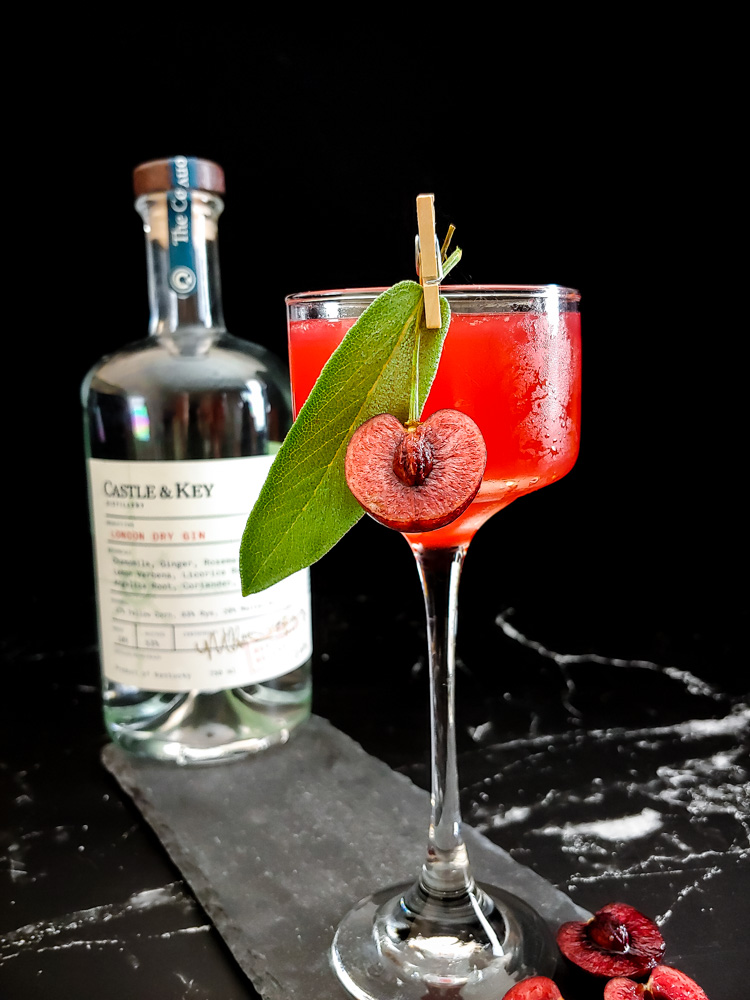 cherry gin smash in a coupe glass with sage and fresh cherry garnish