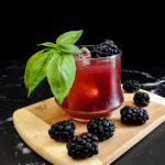 blackberry old fashioned cocktail in a rocks glass with ice and basil and blackberries