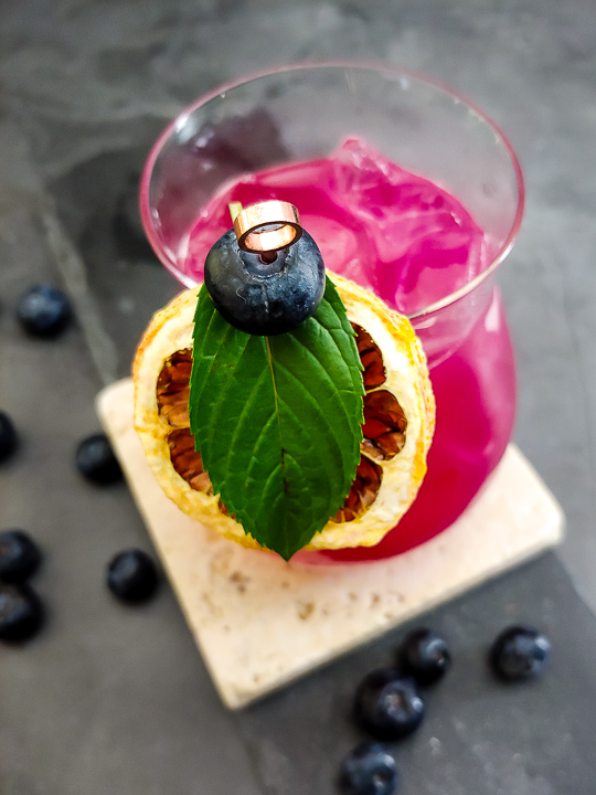 magenta tequila blueberry cocktail with lemon wheel, mint and blueberry garnish