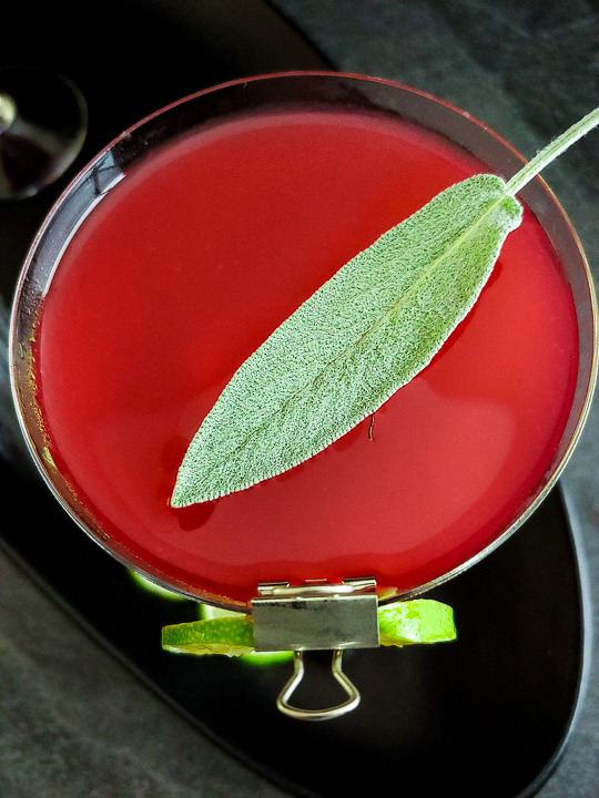 cherry gimlet cocktail with sage leaf and lime wheel garnish