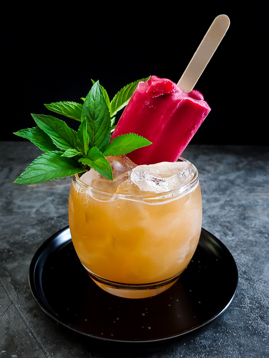 peach cocktail with a raspberry popsicle garnish