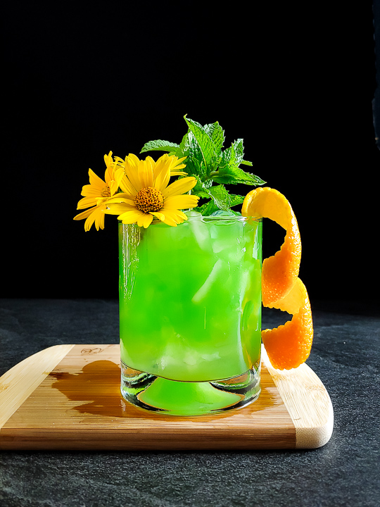 a green mule with mint, orange and flower garnish