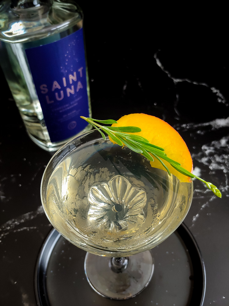 light yellow moonshine manhattan with peach and lavender garnish