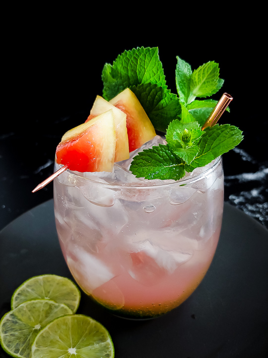 light pink tequila cocktal on rocks with watermelon and mint garnish