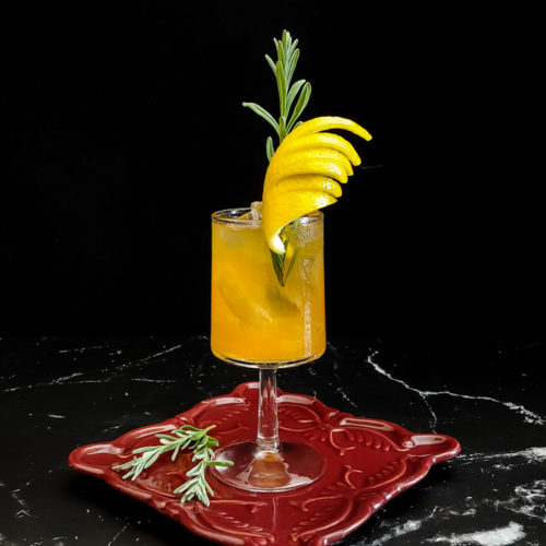 Old fashioned in a wine glass with ice, lemon peel and lavender sprig