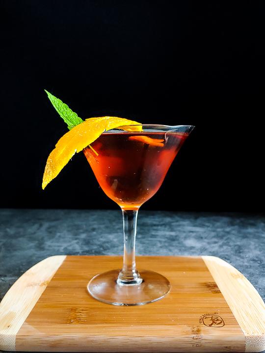 manhattan cocktail with orange leaf cutout garnish