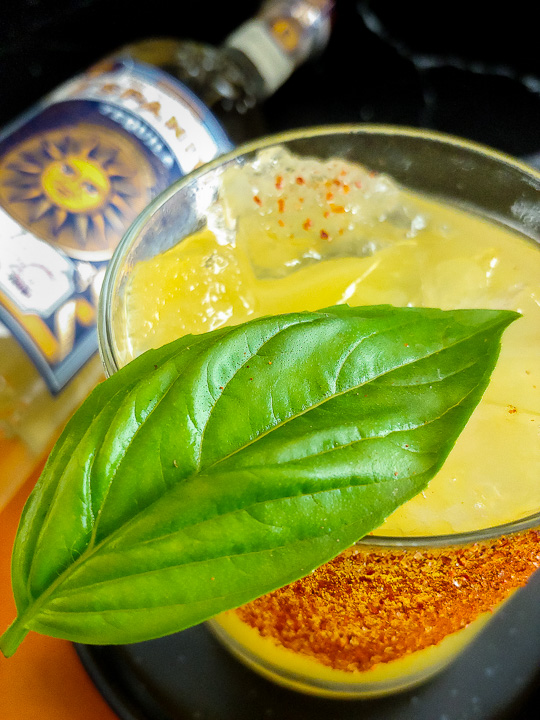 mango cocktail with spiced swath and basil leaf, and tequila bottle