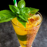 yellow mango cocktail with basil leaves and red chili rim