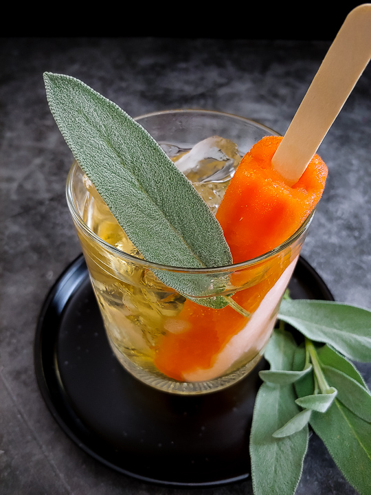 mezcal cocktail with orange popsicle and sage leaf on top