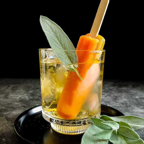 mezcal cocktail with orange popsicle and sage leaf on top