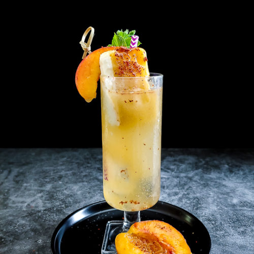 peach cocktail in tall glass garnished with peach, mango popsicle and mint