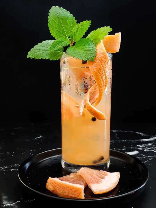 grapefruit paloma cocktail in tall glass, silver tray, grapefruit and verbena garnish
