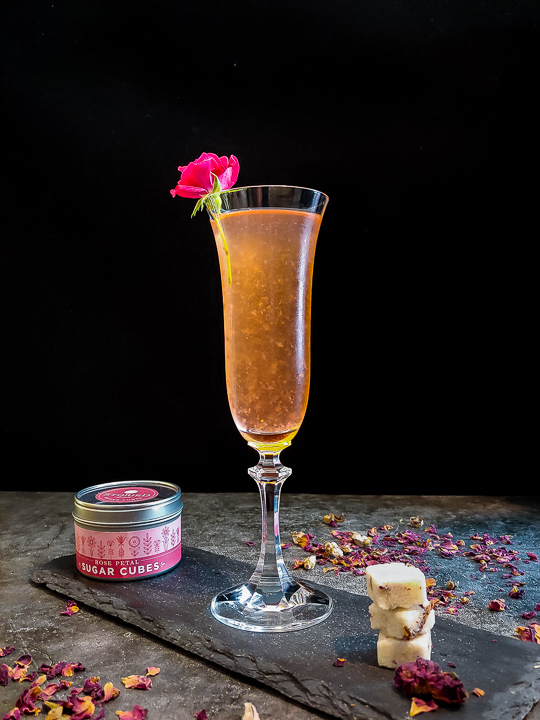 light pink cocktail in champagne flute with rose garnish and sugar cubes
