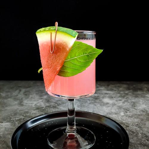watermelon cocktail with watermelon and basil garnish