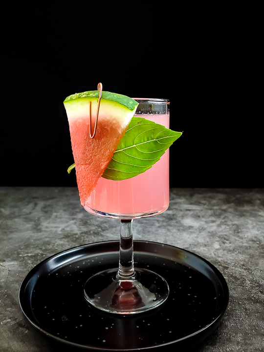 watermelon cocktail with watermelon and basil garnish