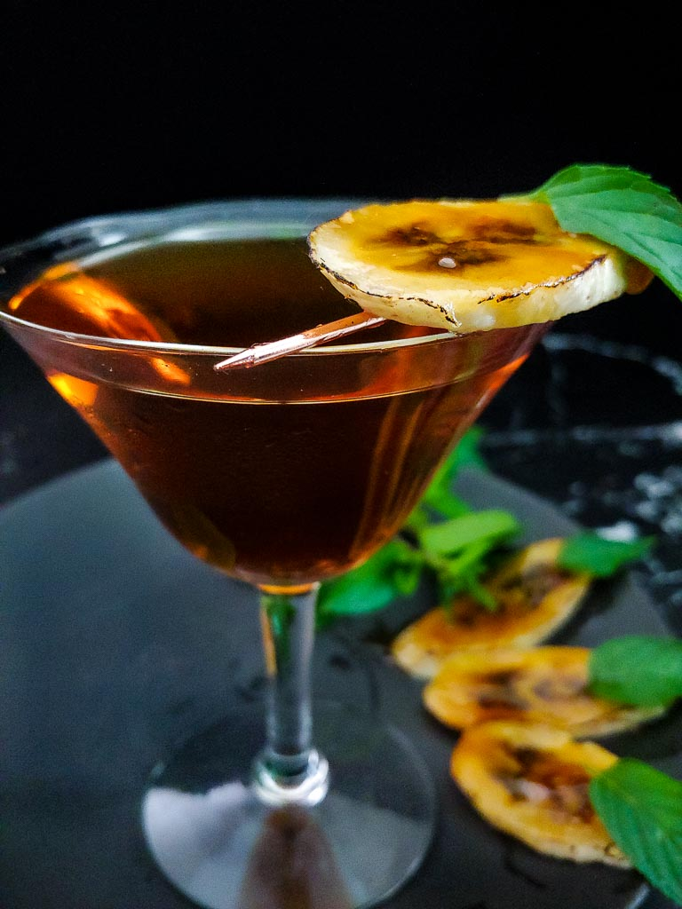 Bananas Foster Manhattan garnished with mint and carmelized banana slices