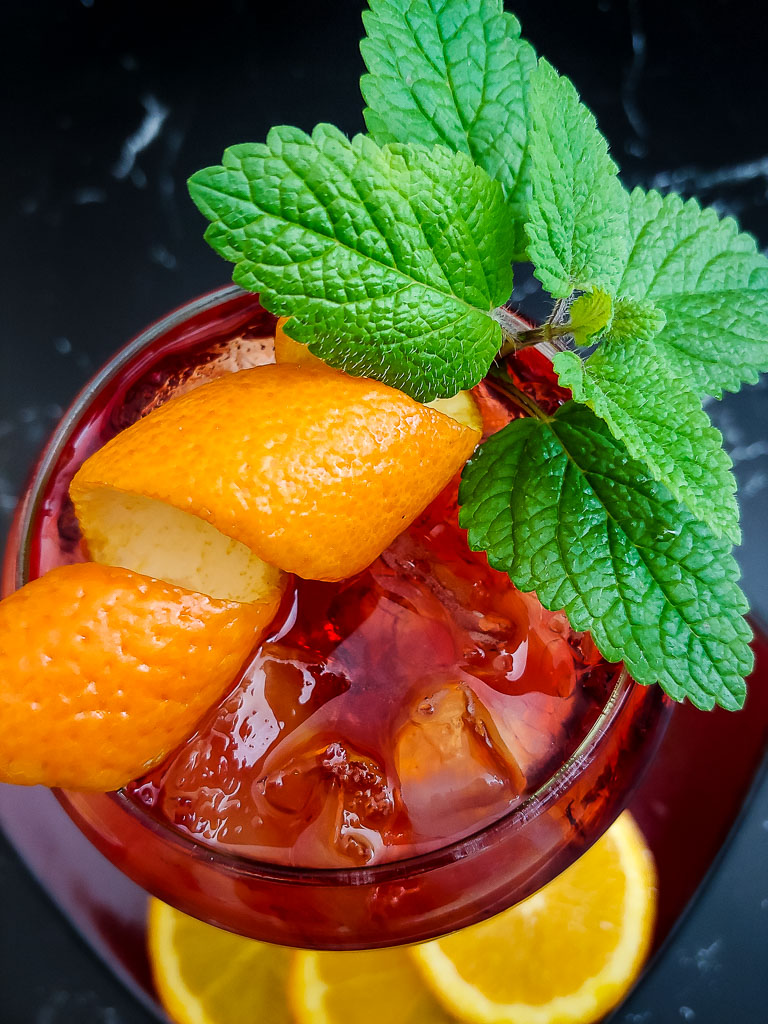 Bitter Bourbon Spritz red cocktail in a wine glass with orange and mint garnish