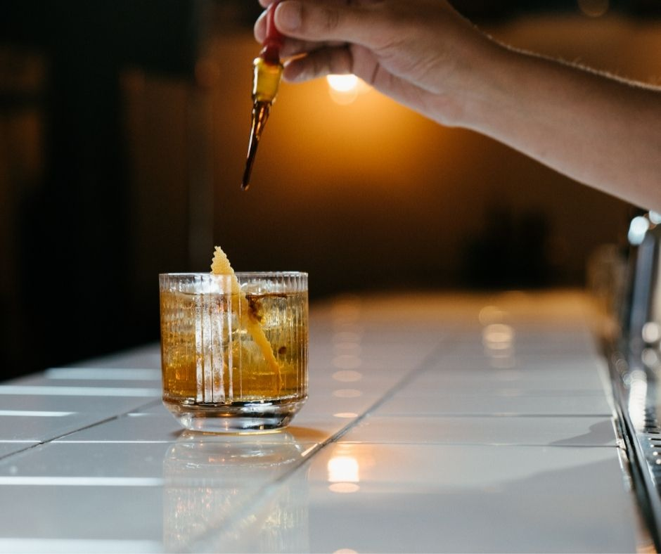 hand dropping bitters into a cocktail