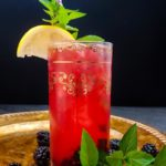 blackberry bourbon cocktail in highball glass with lemon and mint garnish