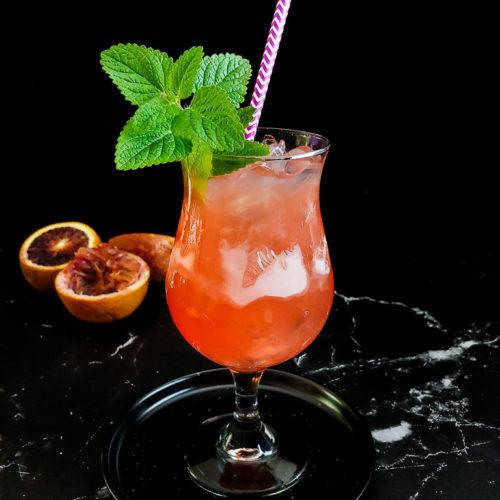 blood orange cooler cocktail with vebena garnish and spent blood oranges