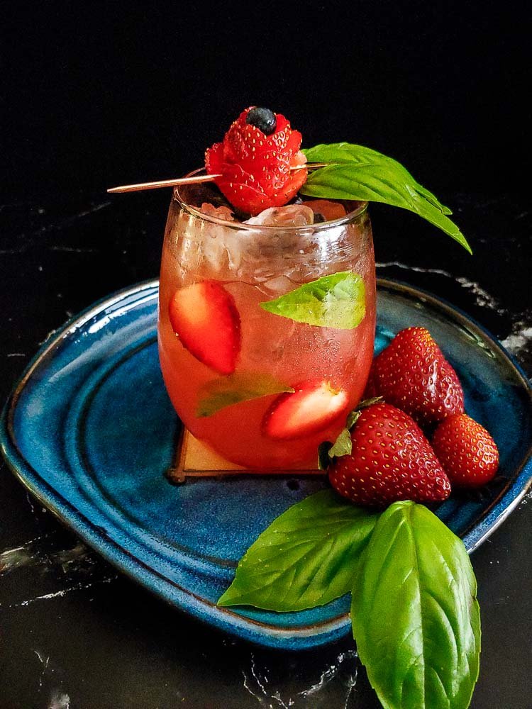 champagne bourbon cooler cocktail with strawberry and basil garnish
