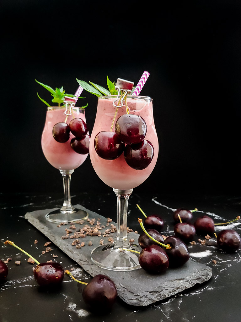 two cherry bourbon milkshakes in wine glasses with mint and cherry garnish