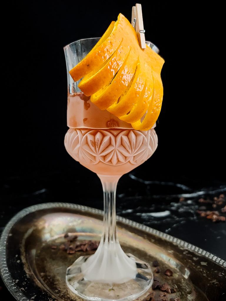 chocolate sazerac with orange garnish, hands moving tray