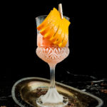 chocolate sazerac with orange garnish