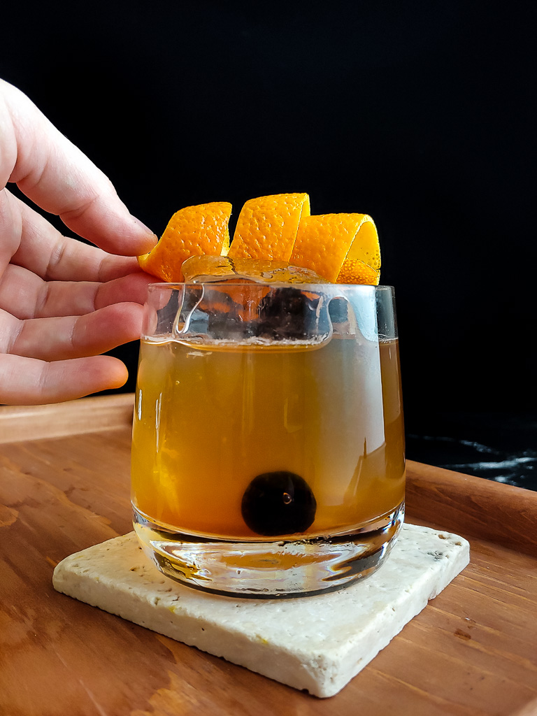 orange twist placed on the top of a classic whiskey sour