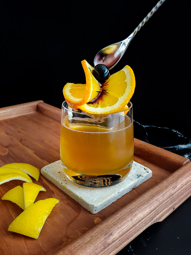 classic whiskey sour with an orange twist and cherry