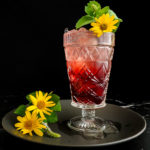 Hibiscus Ginger Mule in a tall glass with flower and mint garnish