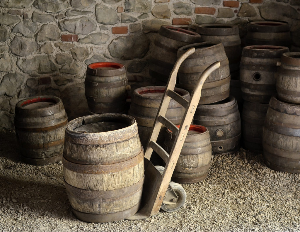 Old barrels against a stone wall with a dolly