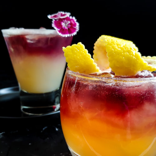 Two versions of New Your Sour garnished with flower and lemon