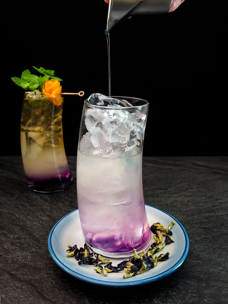 Bourbon cooler in tall glass with purple, white and yellow layer, orange rose and mint garnish