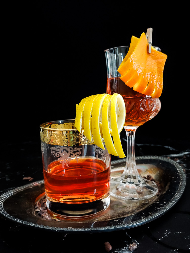 Classic Sazerac in rocks glass with lemon garnish. Chocolate sazerac in wine glass with orange garnish