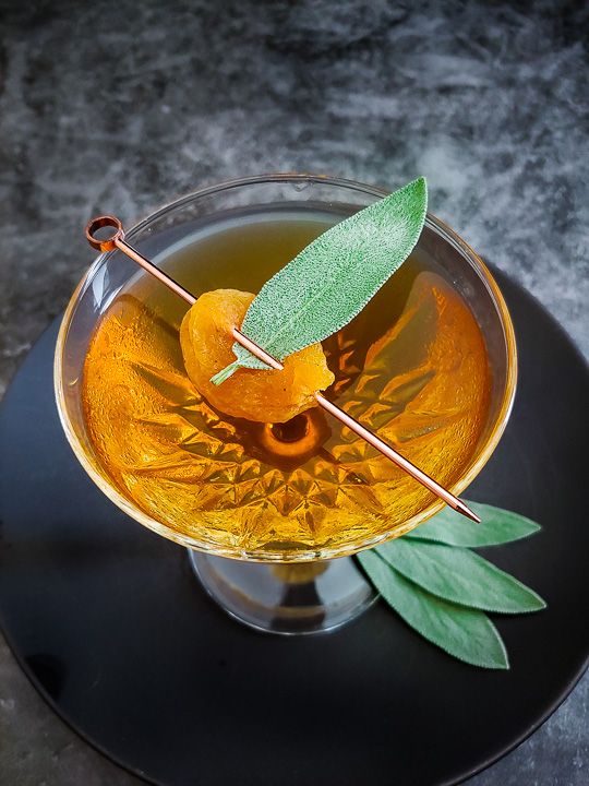 Uncle Nearest Apricot Manhattan cocktail in a coupe glass with apricot with a sage leaf