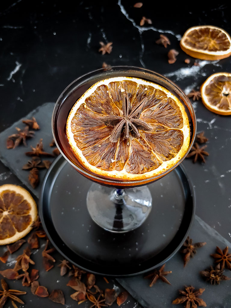 black manhattan with orange chip and star anise garnish
