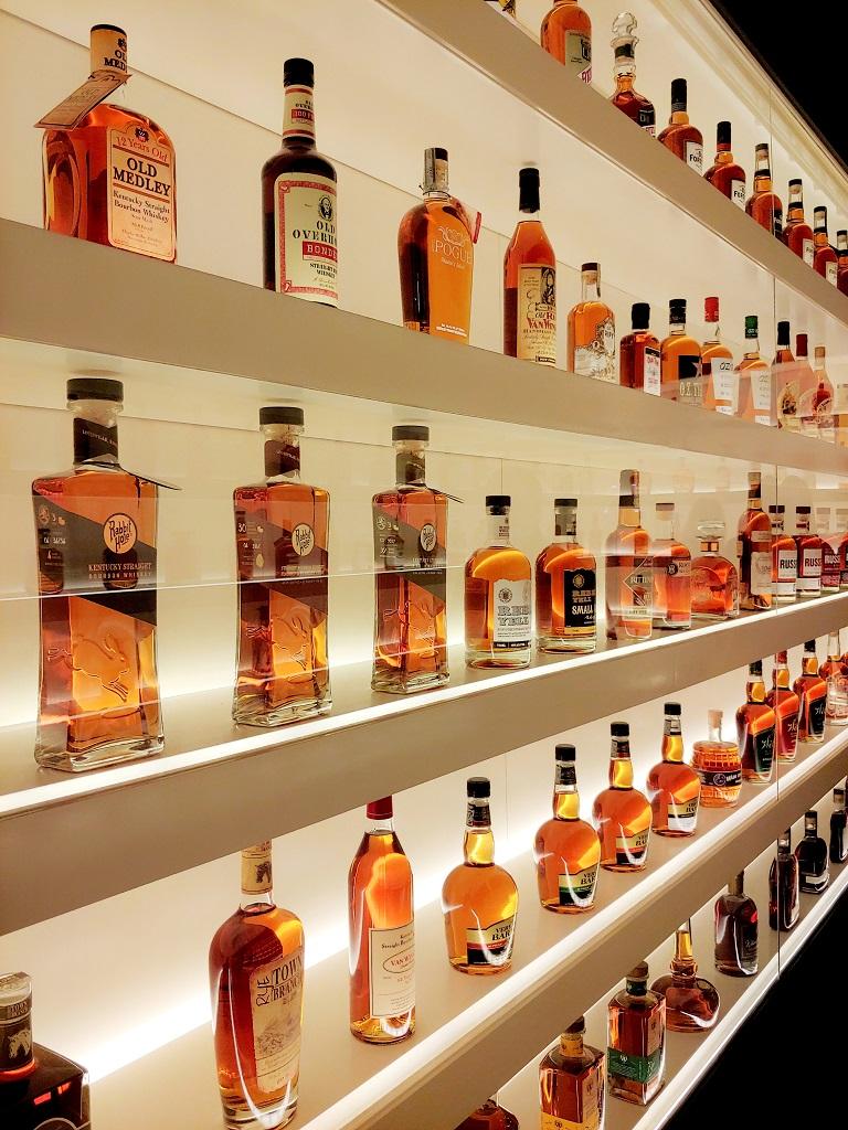 backlit shelves of bourbon
