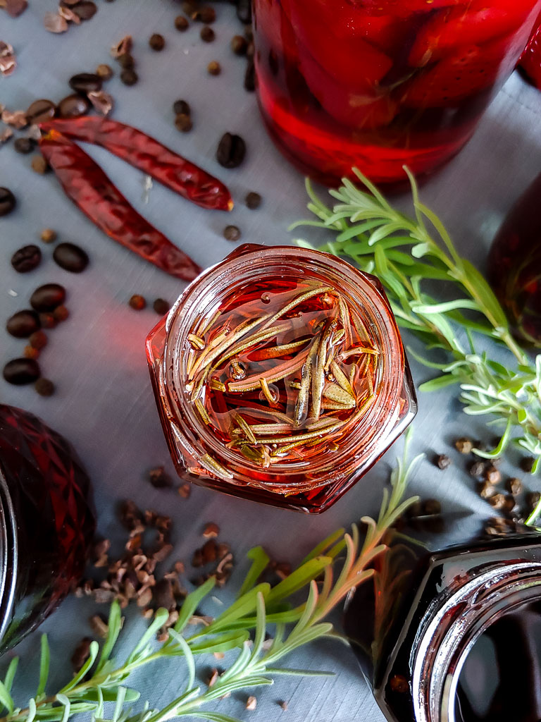 rosemary campari infusion in small glass jar on tray with other jars and infusions