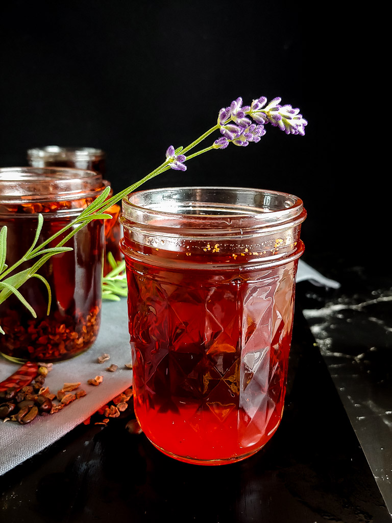 lavender campari infusion in small glass jar with sprig of lavender