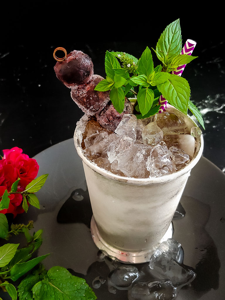 cherry mint julep in julep cup, garnished with mint and cherries