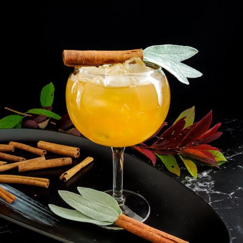 Apple Bourbon Cocktail with cinnamon stick and sage leaf garnish